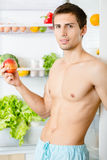 Man keeps apple standing near the fridge Royalty Free Stock Image