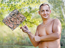 Man keeps barbecue grill with fish. Nature, forest, summer Royalty Free Stock Photography
