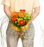 Man keeps bouquet. Behind the back stock images