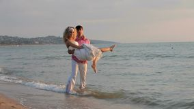 Man Keeps Girl In His Arms. On the seashore stock footage