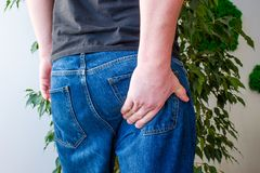 Man keeps hand on lower part of buttocks. Concept photo manifestations of pain at exit of sciatic nerve, inflammation, sciatica or