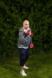 Man keeps himself fit with dumbbell workouts outdoors. He is doing sport Royalty Free Stock Photo