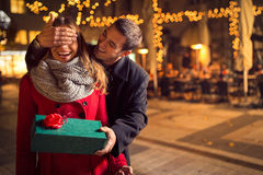 Man  keeps his girlfriend eyes covered while  she giving a gift Stock Photos
