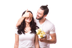 Man keeps his girlfriend eyes covered while she giving a gift. Romantic surprise for Valentine Day. Man look at woman. Caucasian couple. White background Royalty Free Stock Image