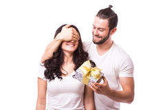 Man keeps his girlfriend eyes covered while she giving a gift. Romantic surprise for Valentine Day. Man look at woman. Caucasian couple. White background Royalty Free Stock Photography
