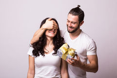 Man keeps his girlfriend eyes covered while she giving a gift. Romantic surprise for Valentine Day. Man look at woman. Caucasian couple. White background Stock Photo