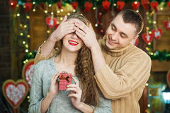 Man keeps his girlfriend eyes covered while she giving gift, romantic surprise for valentines day Royalty Free Stock Photography