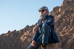 Man in a keffiyeh sitting on a rock in the desert Royalty Free Stock Image