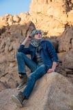 Man in a keffiyeh sitting on a rock in the desert Stock Photo