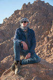 Man in a keffiyeh sitting on a rock in the desert Stock Photography