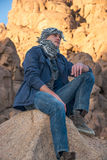 Man in a keffiyeh sitting on a rock in the desert Royalty Free Stock Photography
