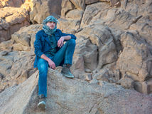 Man in a keffiyeh sitting on a rock in the desert Stock Images
