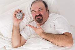 Man kept awake by noisy neighbours. Middle-aged bearded man kept awake by noisy neighbours lying in bed grimacing and pointing to the time on his alarm clock Royalty Free Stock Photos