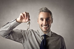 Man with keys. Businessman holding up some keys royalty free stock photos