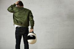 Man in a khaki pilot jacket with helmet Stock Image