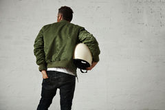 Man in a khaki pilot jacket with helmet Stock Images