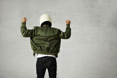 Man in a khaki pilot jacket with helmet. Man in white motorcycle helmet and green pilot jacket shot from the back with both fists up in the air with shaka Stock Photography