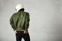 Man in a khaki pilot jacket with helmet Stock Photos