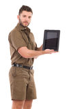 Man in khaki uniform presenting a shockproof digital tablet. Three quarter length studio shot isolated on white Royalty Free Stock Images