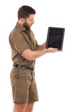 Man in khaki uniform showing a shockproof digital tablet. Royalty Free Stock Image