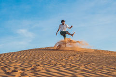 A man is kicking sand in a red desert. Splash of anger concept Stock Photos