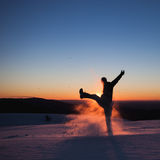 Man kicking snow in winter landscape Stock Photography