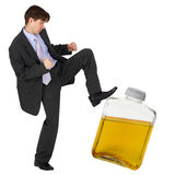 Man kicks a bottle of gasoline. A man kicks a bottle of yellow liquid Royalty Free Stock Image