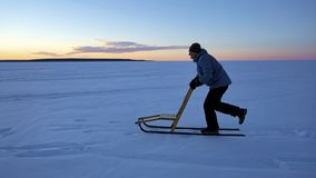 Man kicksledding to stay fit during winter months. A man glides along the ice on a kicksled to stay fit and active during the long winter months in Canada royalty free stock photo