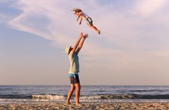 Man with kid outdoors. Man playing with daughter on beach. Rimini, Italy royalty free stock images