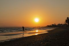 Man and kid silhouette run on the sea shore, on orange sun set backround, vacation evening. Parent and child, Father`s day, Famil