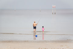 Man and kid walking towards the sea to fish Royalty Free Stock Images