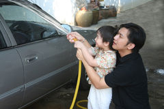 Man & kid washing car. Man and kid washing car in a sunny afternoon happily Stock Images