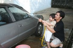 Man & kid washing car. Man and kid washing car in a sunny afternoon happily Royalty Free Stock Photos
