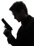 Man killer policeman holding gun portrait silhouette. One man killer policeman holding gun portrait silhouette studio white background royalty free stock photography