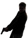 Man killer policeman holding gun walking silhouette. One man killer policeman holding gun walking silhouette studio white background royalty free stock photos