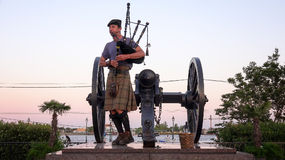 Man in Kilt Playing Bagpipes at Sunset in Jackson Square, New Or Royalty Free Stock Images