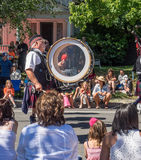 Man in kilts plays a drum in parade. A man wearing a Scottish costume with a kilt plays a large bass drum that entertain the crowd watching the Fourth of July stock photo