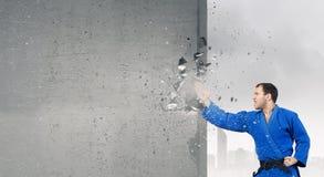Man in kimono breaking wall . Mixed media Royalty Free Stock Images