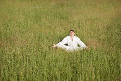 Man in kimono meditates sitting in grass Stock Photo