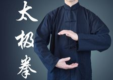 Man in kimono, in a position of tai chi. On blue background Stock Photography