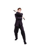 Man in a kimono practicing kung fu with nunchaku Royalty Free Stock Photos