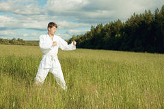 Man in kimono trains karate in open air Stock Photos