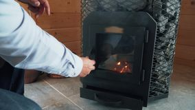 Man kindles the stove in sauna, wood stove in sauna. Small pieces of wood are burning stock video