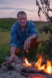 Man kindling bonfire in nature Royalty Free Stock Photography