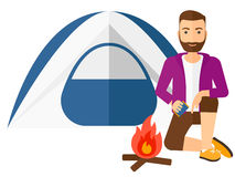 Man kindling fire. A hipster man with the beard kindling a fire in camp vector flat design illustration isolated on white background Royalty Free Stock Images