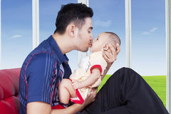 Man kiss his child near the window. Young men holds and kiss his baby while sitting on sofa near the window at home stock image