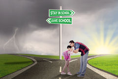 Man kiss his child on the road. Portrait of young father kissing his daughter on the road with road sign to stay or leave school stock image