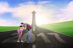 Man kiss his daughter on street. Image of a young men kissing his daughter on the road with number 2017 and upward arrow Royalty Free Stock Photography