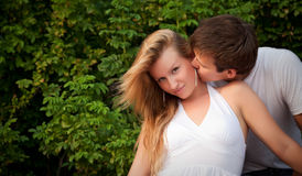 Man kiss sly girl in cheek Stock Photography