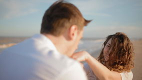 Man kiss woman's hands on  the beach. White couple on the seaside show their feelings.Make takes woman's hands, kiss them. Woman kiss his partner. Wind play in stock video